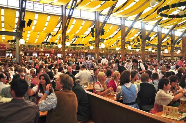 Um multidão bebendo cerveja dentro dos barracões.