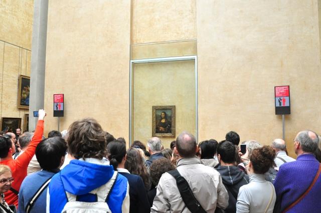 A multidão em frente à Mona Lisa, disputando a melhor foto possível.