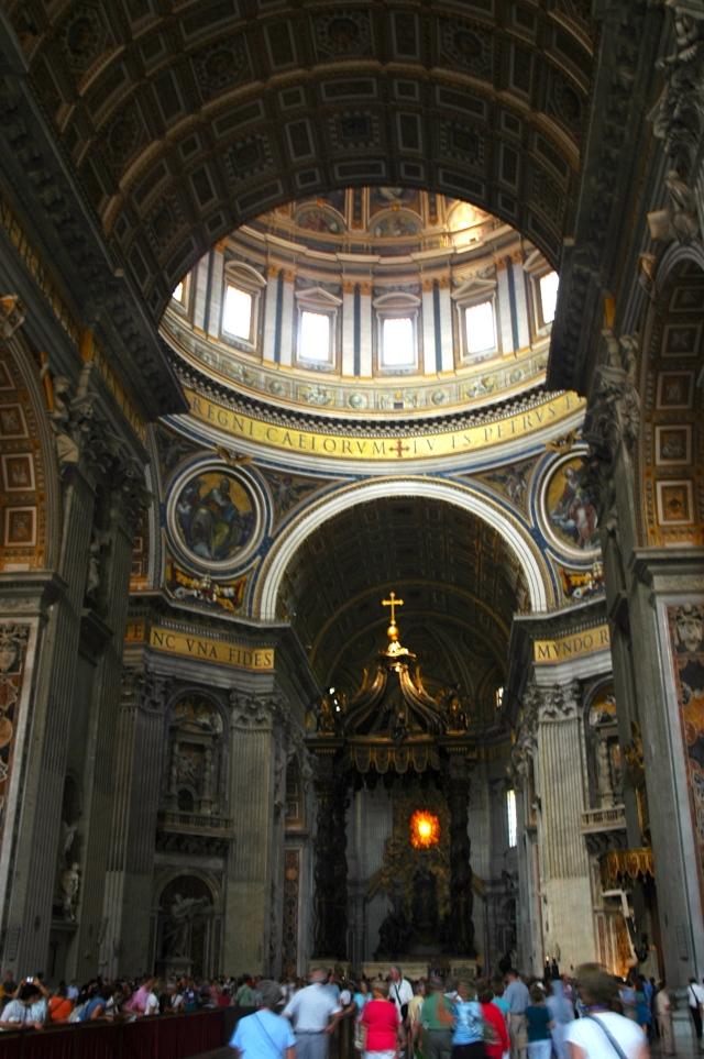 O interior da Basílica de São Pedro com o Domo de Michelangelo ao fundo.