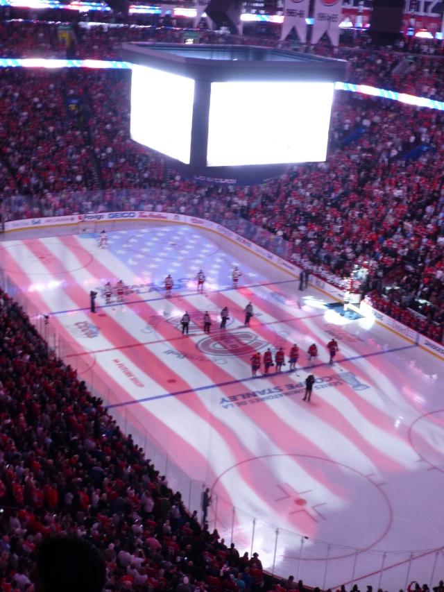 A bandeira americana projetada no piso de gelo na hora do hino nacional.