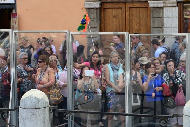 Os turistas observam a fonte através do vidro.