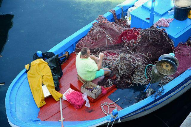 Pescadores consertam redes na costa de Gallipoli.
