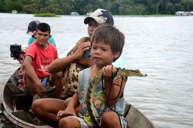 Família de caboclo ganha a vida expondo animais no meio do rio.